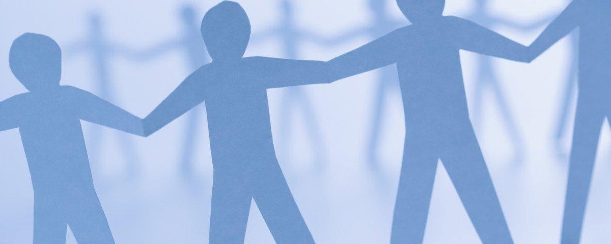 Cutout paper men standing holding hands